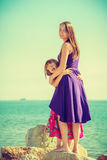Mother and daughter posing at sea rocks Royalty Free Stock Photography