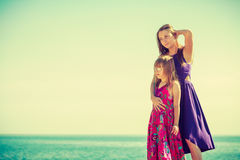 Mother and daughter posing at sea rocks Stock Images