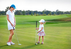Mother and daughter practicing to hit the ball at the course Stock Images
