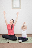 Mother and daughter practicing yoga Stock Photos