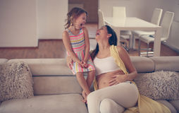 Mother and daughter. Pregnant women and her daughter enjoy at home Royalty Free Stock Photography