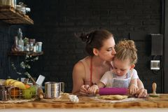 Mother and daughter prepare cookies in kitchen stock photos