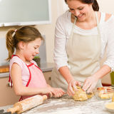 Mother and daughter prepare dough home cake. Mother and daughter prepare dough baking apple cake happy together Stock Photography
