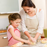 Mother and daughter prepare dough home cake. Mother and daughter prepare dough baking apple cake happy together Royalty Free Stock Photo