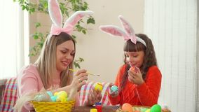 Mother and daughter are prepared for a happy Easter and paint eggs, my daughter keeps eggs painted like eyes. Mother and daughter are prepared for a happy stock video footage