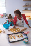 Mother and daughter preparing cookies in kitchen worktop stock photography