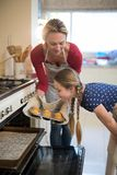 Mother and daughter preparing cup cake in kitchen Stock Photos
