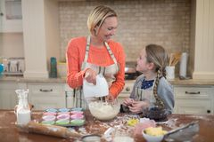Mother and daughter preparing cup cake in kitchen Royalty Free Stock Photo