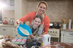 Mother and daughter preparing cup cake in kitchen Royalty Free Stock Photos