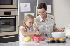 Mother And Daughter Preparing Cupcakes Royalty Free Stock Images