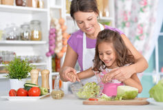 Mother and daughter preparing dinner. Together on kitchen Stock Photos
