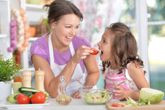 Mother and daughter preparing dinner. Together on kitchen Royalty Free Stock Photos