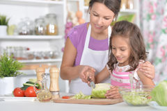 Mother and daughter preparing dinner. Together on kitchen Royalty Free Stock Photo
