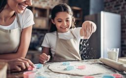 Mother and daughter preparing dough for cookies stock image