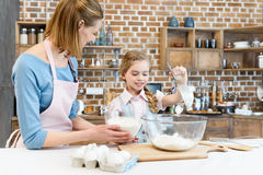 Mother and daughter preparing dough and cooking together in kitchen. Happy mother and daughter preparing dough and cooking together in kitchen stock image