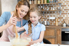 Mother and daughter preparing dough in glass bowl at kitchen. Happy mother and daughter preparing dough in glass bowl at kitchen royalty free stock photo