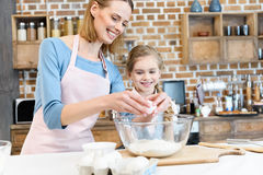 Mother and daughter preparing dough for home baking in kitchen. Happy mother and daughter preparing dough for home baking in kitchen stock photos