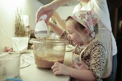 Mother and daughter preparing dough in the kitchen Stock Images