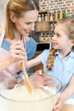 Mother and daughter preparing dough and looking at each other Stock Photo