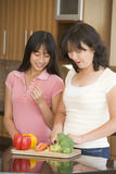 Mother And Daughter Preparing Meal Stock Images