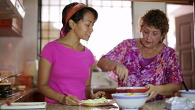 Mother daughter preparing meal together in kitchen