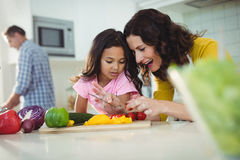 Mother and daughter preparing salad in kitchen Stock Photos