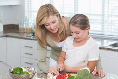 Mother and daughter preparing salad together Stock Photo