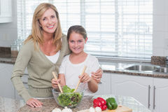Mother and daughter preparing salad together Stock Images