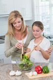 Mother and daughter preparing salad together Royalty Free Stock Photos