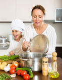 Mother and daughter preparing soup Stock Images