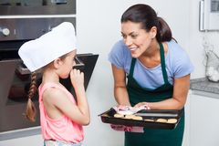 Mother and daughter preparing taking cookies oven Royalty Free Stock Image