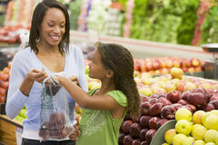 Mother and daughter in produce section Royalty Free Stock Photo