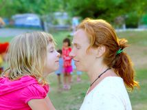 Mother and daughter profile playing in park Royalty Free Stock Images