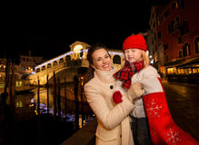 Mother and daughter pulling gift from Christmas sock in Venice Stock Photos