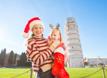Mother with daughter pulling out gift from Christmas sock, Pisa Royalty Free Stock Photos