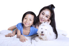 Mother and daughter with puppy on studio stock photos