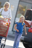 Mother with daughter pushing grocery cart full of groceries royalty free stock photography