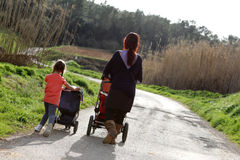 Mother and daughter pushing prams Royalty Free Stock Image