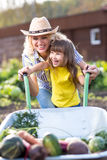 Mother and Daughter pushing Wheelbarrow with Royalty Free Stock Images