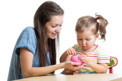 Mother and daughter put coins into piggy bank Stock Photo