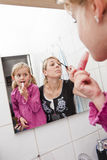 Mother and daughter put on make-up Royalty Free Stock Photos