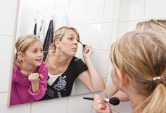 Mother and daughter put on make-up Royalty Free Stock Image