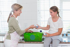 Mother and daughter putting bottles in recycling box Stock Image