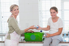 Mother and daughter putting bottles in recycling box Royalty Free Stock Photo