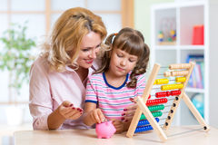 Mother and daughter putting coins into piggy bank Royalty Free Stock Photos