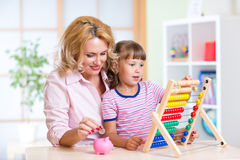 Mother and daughter putting coins into piggy bank Stock Images