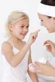 Mother and daughter putting cream on face Stock Photo