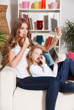 Mother and daughter putting lipstick on Stock Photo