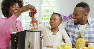 Mother and daughter putting strawberries in juicer. At home stock footage