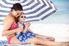 Mother And Daughter Putting On Sun Cream Royalty Free Stock Images